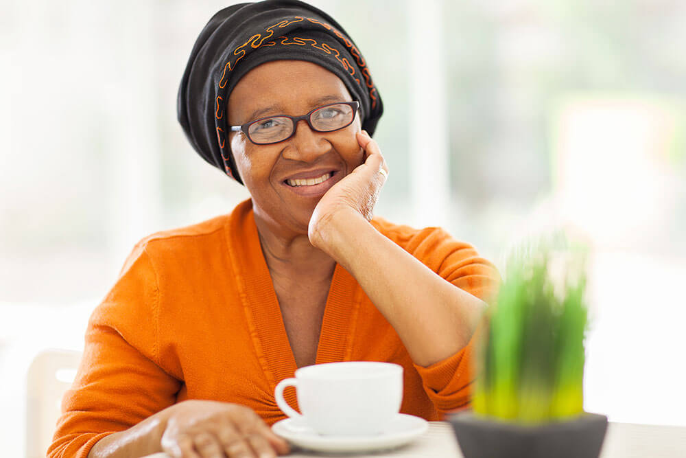 Smiling woman sitting at table with a coffee mug in front of her