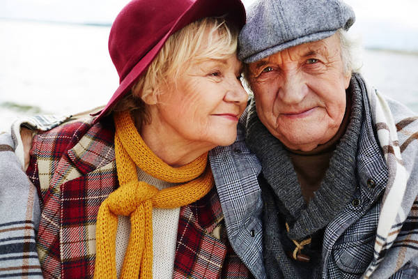 Senior couple wearing hats and scarves with plaid patterns.