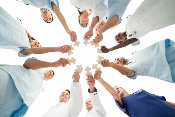 Doctors standing in a circle holding puzzle pieces to represent different areas of patient care.