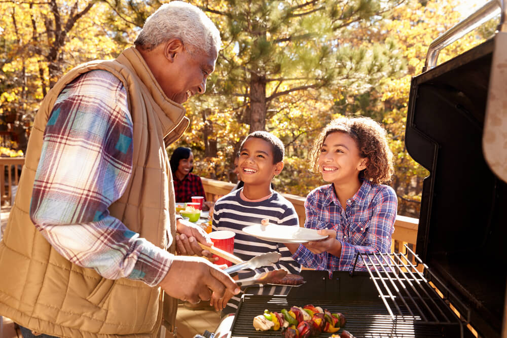 grandfather at bbq with grandkids in autumn setting