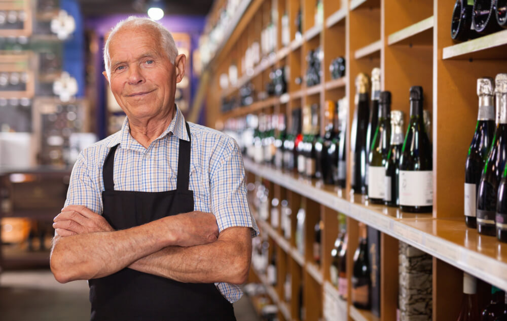 senior man in apron in wine shop