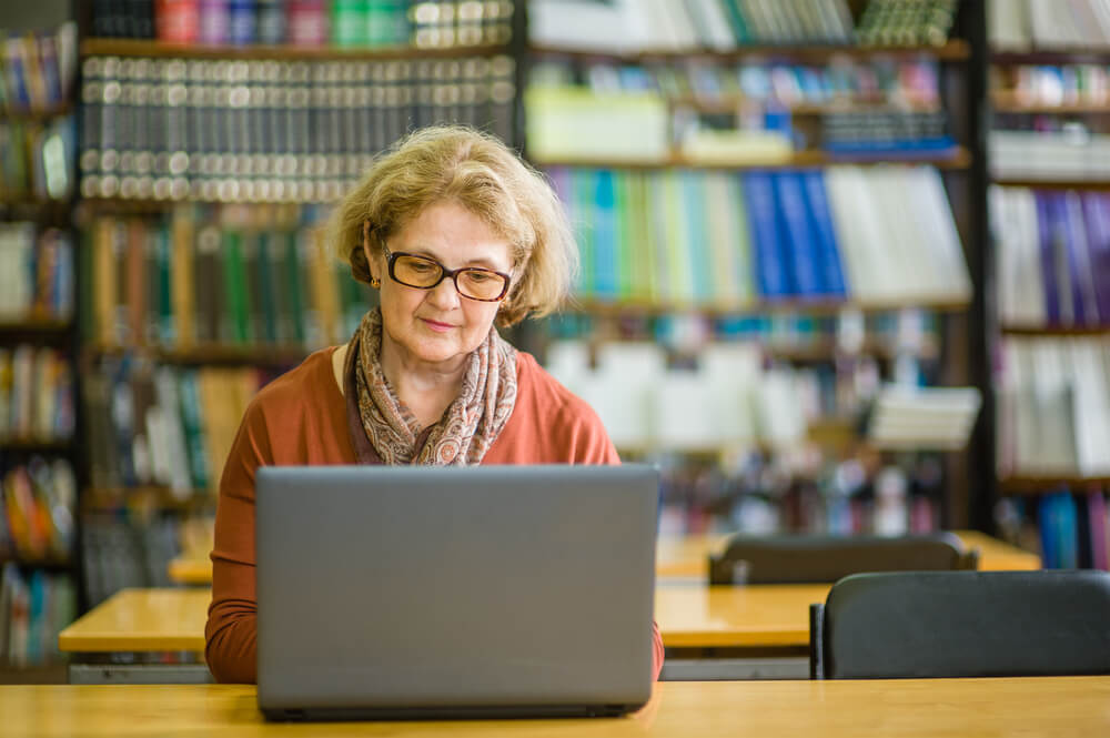 Senior woman in glasses on laptop at library